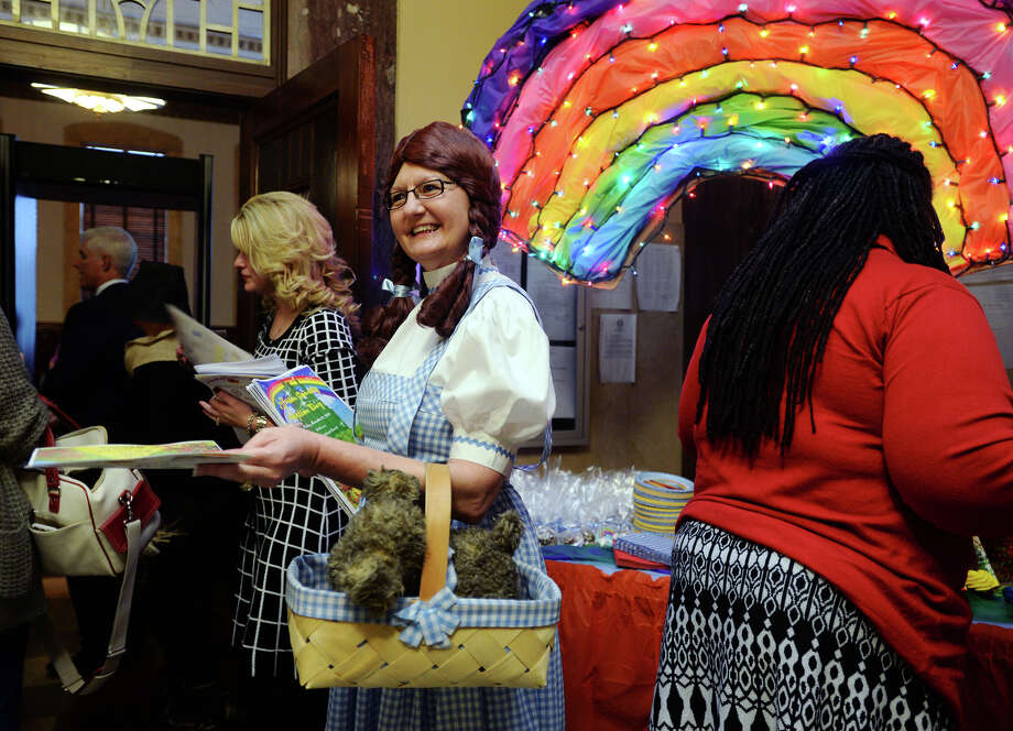 """Cindy Torrans with the Jefferson County Bar Association hands out programs while dressed as Dorothy from """"The Wizard of Oz"""" on Friday morning. Friday's adoption ceremony's theme was """"There's No Place Like Home."""" Judge Randy Shelton oversaw the adoption of 29 children by 19 families during the National Adoption Day celebration at the Jefferson County Courthouse on Friday. The group adoption ceremony comes one day before National Adoption Day, which raises awareness of the more than 100,000 children in foster care and is usually celebrated the last Saturday before Thanksgiving. Photo taken Friday 11/21/14 Jake Daniels/The Enterprise Photo: Jake Daniels / ©2014 The Beaumont Enterprise/Jake Daniels"""