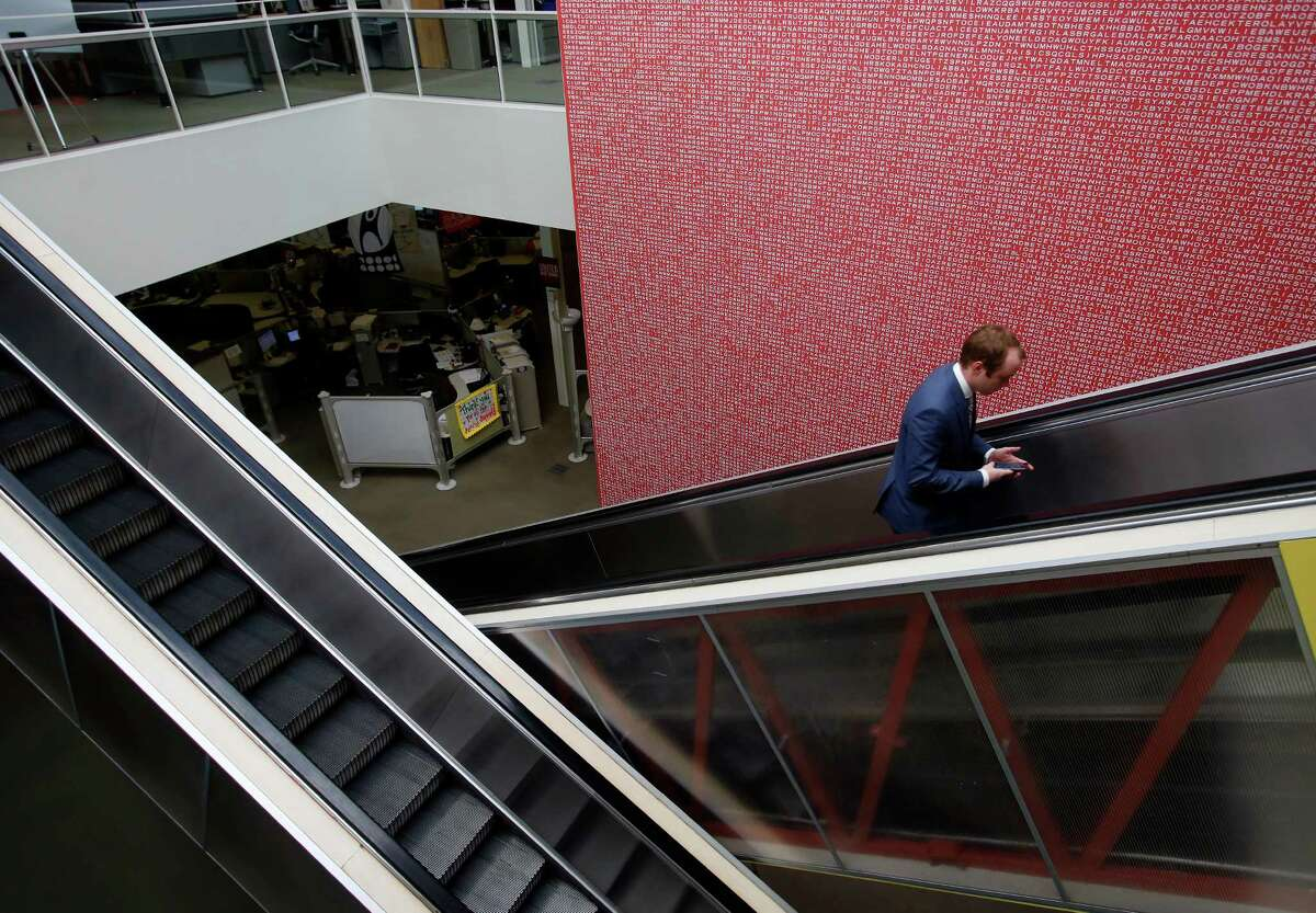 An employee rides an escalator past a giant word find -- that at one time was the largest one in the world -- at the Rackspace Hosting offices Wednesday, Nov. 19, 2014.