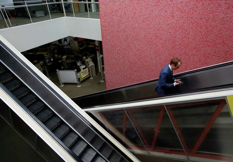 An employee rides an escalator past a giant word find -- that at one time was the largest one in the world -- at the Rackspace Hosting offices Wednesday, Nov. 19, 2014. Photo: William Luther /San Antonio Express-News / © 2014 San Antonio Express-News