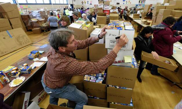 Concerned for the Hungry Inc. volunteer Larry Lewis sets up boxes of donated Thanksgiving Day food items Friday morning, Nov. 21, 2014, at the Keane Elementary School in Schenectady, N.Y. The food is to be distributed for at home Thanksgiving Dinners.  (Skip Dickstein/Times Union) Photo: SKIP DICKSTEIN / 00029587A