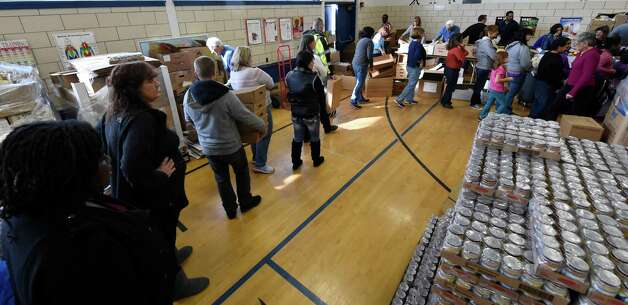 Volunteers with Concerned for the Hungry Inc. set up a bucket brigade of donated Thanksgiving Day food items Friday morning, Nov. 21, 2014, at the Keane Elementary School in Schenectady, N.Y. The food is to be distributed for at home Thanksgiving Dinners.  (Skip Dickstein/Times Union) Photo: SKIP DICKSTEIN / 00029587A