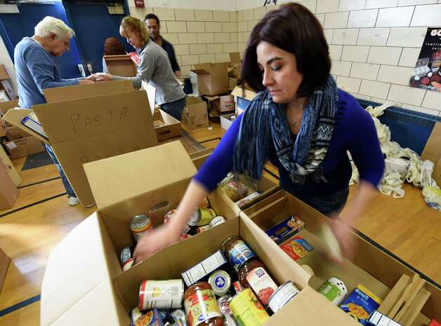 Bridget Cox of the Schenectady Community Action Program collates boxes of donated food items for Thanksgiving meals Friday morning, Nov. 21, 2014, at the Keane Elementary School in Schenectady, N.Y. Concerned for the Hungry Inc. volunteers assembled boxes of food for the needy to use for their Thanksgiving Dinner at home.  (Skip Dickstein/Times Union) Photo: SKIP DICKSTEIN / 00029587A