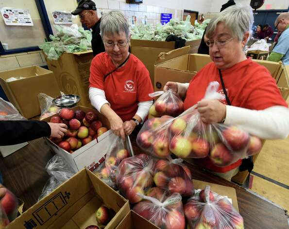 Twins, Amy Davis, left, and Kathleen VanDerstyne package fresh apples for Thanksgiving meals Friday morning, Nov. 21, 2014, at the Keane Elementary School in Schenectady, N.Y. The Concerned for the Hungry Inc. volunteers assembled boxes of food to be distributed for at home  Thanksgiving Dinners.  (Skip Dickstein/Times Union) Photo: SKIP DICKSTEIN / 00029587A