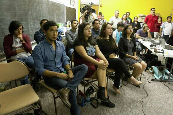 Several dozen at a watch party hosted by United We Dream Houston and Youth Empowerment Alliance listen to President Obama's announcement of a broad executive order of the immigration policy on Thursday, Nov. 20, 2014. ( J. Patric Schneider / For the Chronicle )
