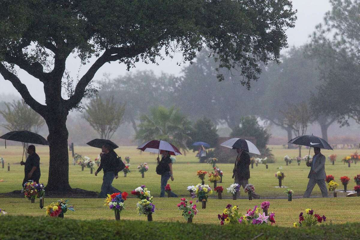 """Mourners cross the Grand View Memorial Park on their way to the funeral home for services for brothers Robert Tisnado, 39, and Gilbert """"Gibby"""" Tisnado, 48, who died in a hazardous chemical leak at a DuPont plant in La Porte last week."""