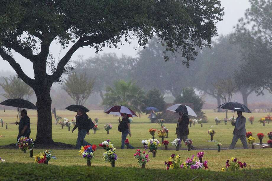"""Mourners cross the Grand View Memorial Park on their way to the funeral home for services for brothers Robert Tisnado, 39, and Gilbert """"Gibby"""" Tisnado, 48, who died in a hazardous chemical leak at a DuPont plant in La Porte last week.  Photo: Johnny Hanson, Staff / © 2014  Houston Chronicle"""