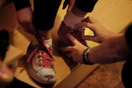 Suzy Loftus (right),  assistant director, division of law enforcement, Office of the Attorney General, helps her 7-year old daughter, Vivienne Loftus, put on her shoes as they prepare to leave the house and walk to school on Monday, November 17, 2014 in San Francisco, Calif.
