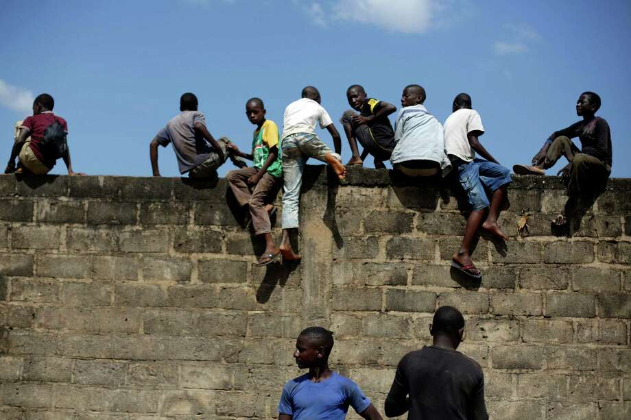 Children out of school climb a wall to see a civilian helicopter land in Gueckedou, Ginea, Friday Nov. 21, 2014. Saturday Nov. 15, 2014. Officials in Guinea say bandits during a roadside robbery stole a cooler containing blood samples that are believed to have Ebola, from a vehicle traveling from Kankan prefecture in central Guinea to a test site in Gueckedou, in the south.(AP Photo/Jerome Delay) Photo: Jerome Delay, STF / AP