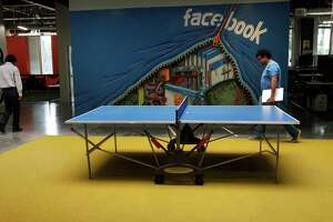 People walk past a ping-pong table and the first Facebook mural in one of the office buildings on the Facebook campus Nov. 12, 2014 in Menlo Park, Calif.