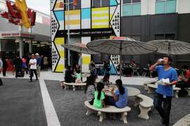 People eat and mill about in front of a burger and snack shop and the arcade on the Facebook campus Nov. 12, 2014 in Menlo Park, Calif.