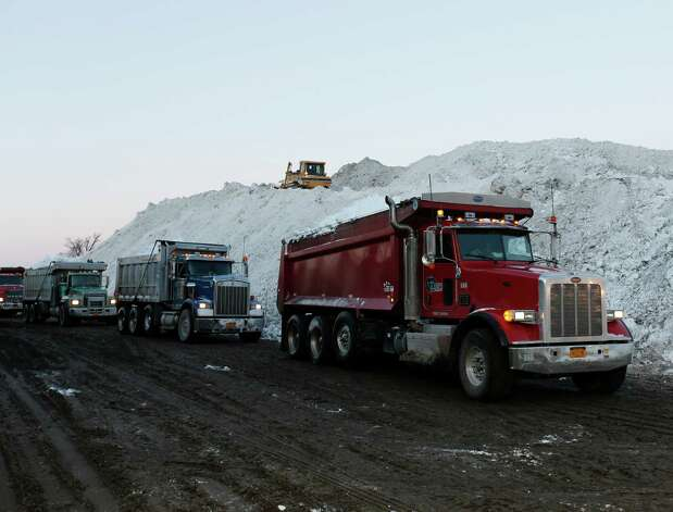 Dump trucks wait to unload snow at the Central Terminal that was removed from south Buffalo neighborhoods after heavy lake-effect snowstorms on Friday, Nov. 21, 2014, in Buffalo, N.Y.  A snowfall that brought huge drifts and closed roads in the Buffalo area finally ended Friday, yet residents still couldn't breathe easy, as the looming threat of rain and higher temperatures through the weekend and beyond raised the possibility of floods and more roofs collapsing under the heavy loads. (AP Photo/Mike Groll) ORG XMIT: NYMG102 Photo: Mike Groll / AP