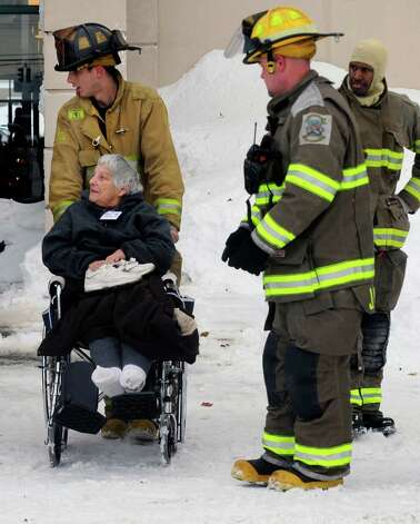 Firefighters from Cheektowaga and Depew assist a patient from from Garden Gate Health Care Facility to the Appletree Mall in Cheektowaga, N.Y.,  Thursday, Nov. 20, 2014. About 180 patients from the facility were moved after officials questioned sustainability of the the roof from the  snowfall.   Roofs began to creak and collapse under the weight of excessive snow as another storm Thursday added to epic snowfall in western New York state. (AP Photo/Gary Wiepert) ORG XMIT: NYGW108 Photo: Gary Wiepert / FR170498 AP