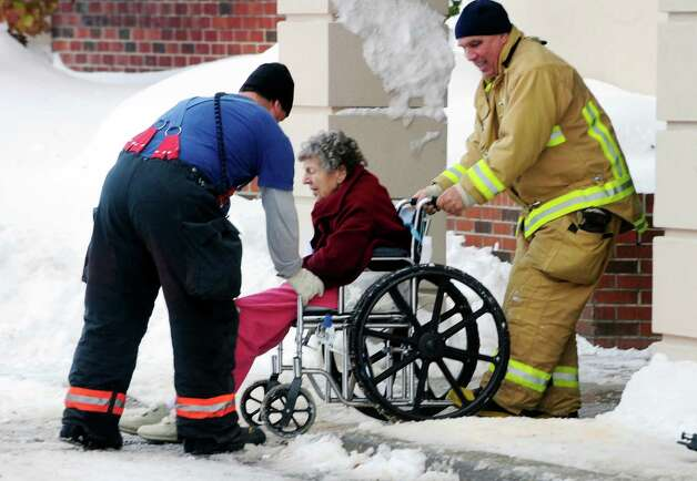 Firefighters from Cheektowaga and Depew assist an elderly patient from from Garden Gate Health Care Facility to the Appletree Mall in Cheektowaga, N.Y.,  Thursday, Nov. 20, 2014. About 180 patients from the facility were moved after officials questioned sustainability of the the roof from the  snowfall.   Roofs began to creak and collapse under the weight of excessive snow as another storm Thursday added to epic snowfall in western New York state. (AP Photo/Gary Wiepert) ORG XMIT: NYGW112 Photo: Gary Wiepert / FR170498 AP