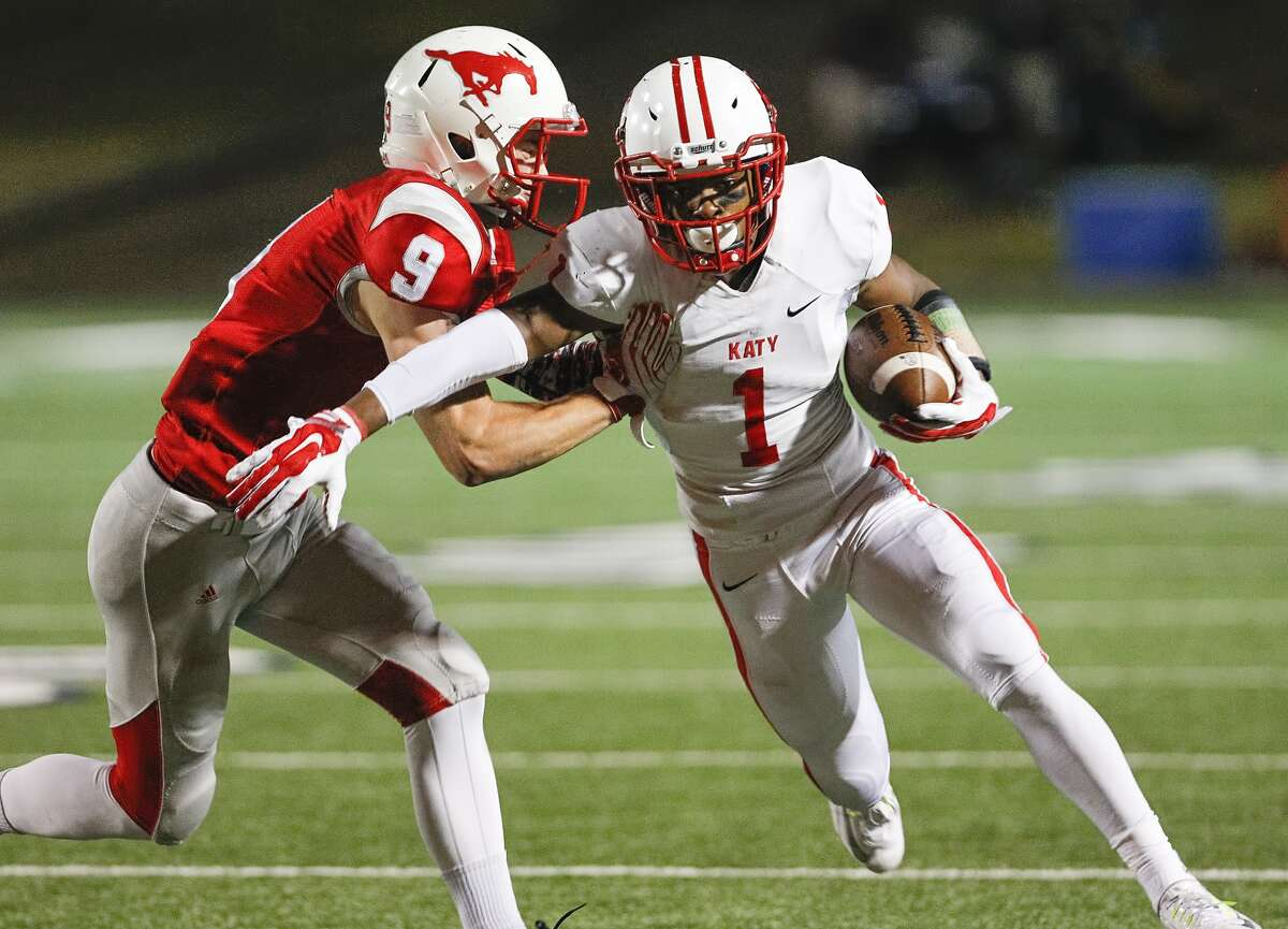 Katy's Tony Mullins attempts to get by defender Tyler Dore of Houston Memorial as the two teams faced off in the 6A Region III playoffs at Tully Stadium on November 21, 2014.