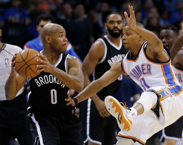 Brooklyn Nets' Jarrett Jack (0) looks to pass around Oklahoma City Thunder's Sebastian Telfair (31) during the third quarter of an NBA basketball game in Oklahoma City, Friday, Nov. 21, 2014. Brooklyn won 94-92. (AP Photo/Sue Ogrocki) ORG XMIT: OKSO120 Photo: Sue Ogrocki / AP