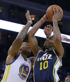 Utah Jazz guard Alec Burks, right, shoots against Golden State Warriors' Marreese Speights during the first half of an NBA basketball game Friday, Nov. 21, 2014, in Oakland, Calif. (AP Photo/Ben Margot)