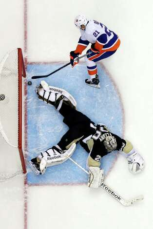 New York Islanders' Kyle Okposo (21) gets a game-winning shot past Pittsburgh Penguins goalie Marc-Andre Fleury (29) in a shootout of an NHL hockey game in Pittsburgh Friday, Nov. 21, 2014. The Islanders won 5-4. (AP Photo/Gene J. Puskar) ORG XMIT: PAGP112 Photo: Gene J.Puskar / AP