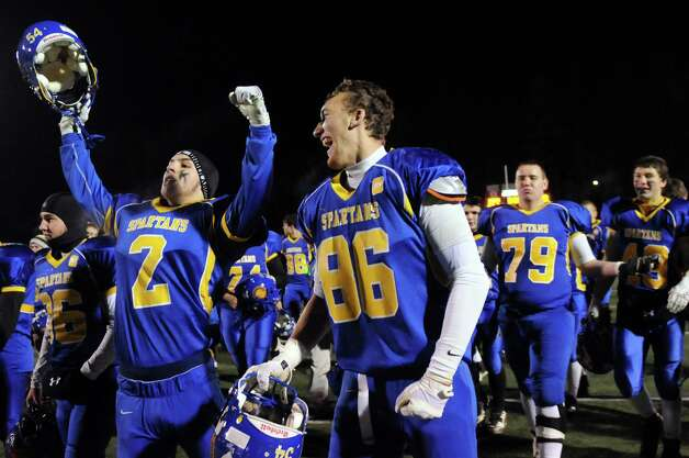 Queensbury's Terry Karanikas, left, and Keeghan O'Leary, center, join the team as they celebrate their 28-21 win over Cornwall in their Class A football state semifinal on Friday, Nov. 21, 2014, at Dietz Stadium in Kingston, N.Y. (Cindy Schultz / Times Union) Photo: Cindy Schultz / 00029566A