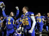 Queensbury's Terry Karanikas, left, and Keeghan O'Leary, center, join the team as they celebrate their 28-21 win over Cornwall in their Class A football state semifinal on Friday, Nov. 21, 2014, at Dietz Stadium in Kingston, N.Y. (Cindy Schultz / Times Union)