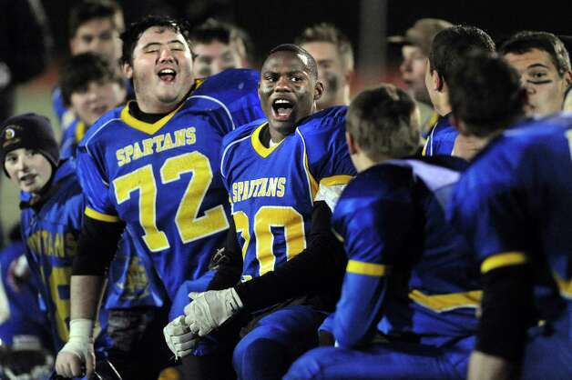 Queensbury's Paul Schiavi (72), left, and Tyrell Adams, center, cheer when teammate Jeffrey Underhill is named best defensive player following their 28-21 win over Cornwall in their Class A football state semifinal on Friday, Nov. 21, 2014, at Dietz Stadium in Kingston, N.Y. (Cindy Schultz / Times Union) Photo: Cindy Schultz / 00029566A