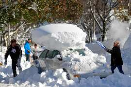 BUFFALO, NY - NOVEMBER 21: Michael Palmer and Carin Schultz work to clear her car of snow and remove it from Union street  on November 20, 2014 in the suburb of Hamburg, Buffalo, New York. The record setting Lake effect snowstorm dumped up to six feet of snow in less than 24 hours closing a one hundred mile section of The New York State Thruway as well as other major roads around Buffalo. Twelve deaths have already been attributed to the storm and with warming temperatures and  rainfall in the forecast epic flooding is expected.  (Photo by John Normile/Getty Images) *** BESTPIX ***