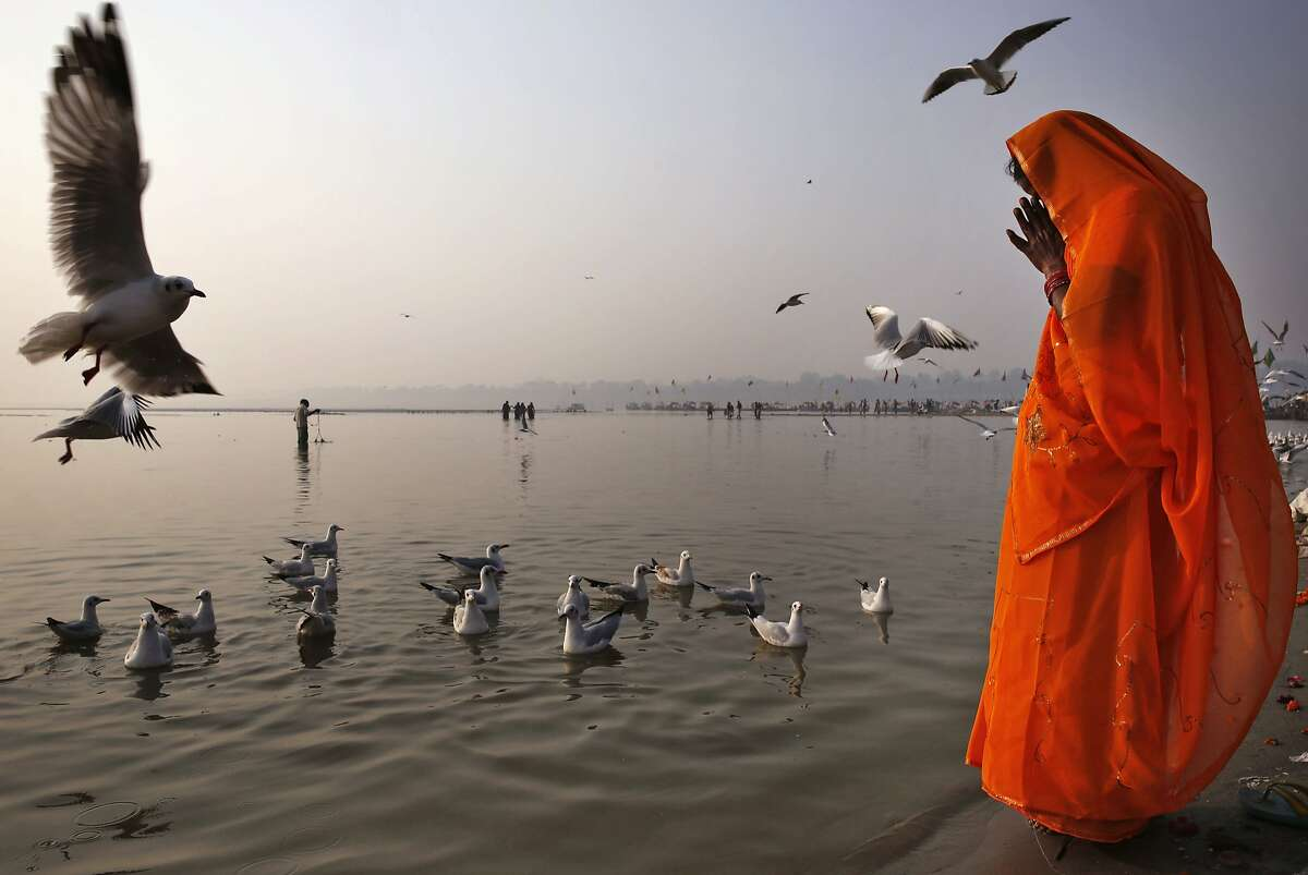 A Hindu devotee prays on the banks of the River Ganges in Allahabad, India, Friday, Nov. 21, 2014. Allahabad, on the confluence of the rivers Ganges, Yamuna and the mythical Saraswathi, is one of Hinduism's important centers. (AP Photo/Rajesh Kumar Singh)