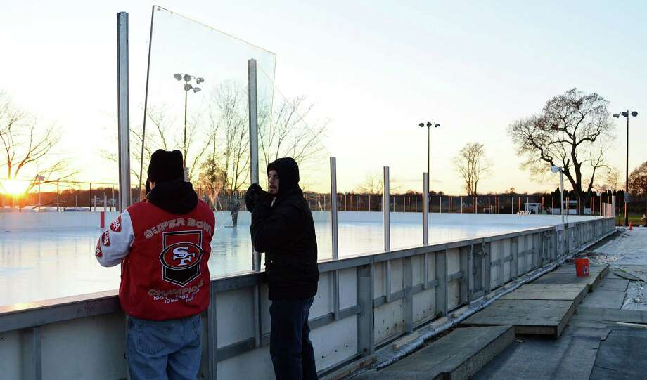 Jeff Incerto, left, and Eric Day install safety glass at the Westport PAL ice rink at Longhsore on Friday evening. Photo: Jarret Liotta / Westport News