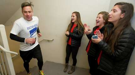 """Brian Hawe is cheered on by Jessica Freiheit, left, Michelle Mato, center, and Ariana Longo, right, as he climbs past the 14th floor during the American Lung Association's 6th annual """"Fight for Air: Tackle Trump Parc"""" stair climb event in Stamford, Conn., on Saturday, November 22, 2014."""