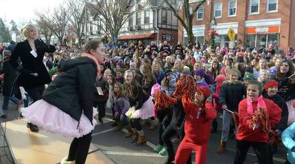 """On a riser, with Zoe Butchen, right, Jean Cobelli, director of Enchanted Garden dance studio, in Ridgefield, leads a street full of supporters in dance moves to Taylor Swift's """"Shake It Off"""" to raise money for the """"Dance, Shake & Donate"""" campaign to benefit the Michael J. Fox Foundation on Saturday morning, November 22, 2014. Main Street in downtown Ridgefield, Conn, was closed to allow the group to make a video that they hope will raise funds for Parkinson's research."""