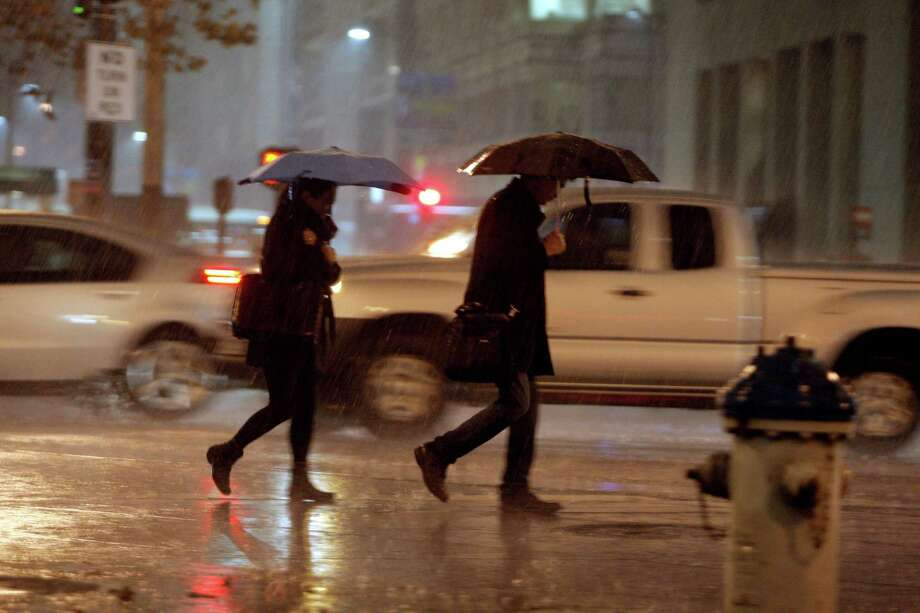 People walk in the pouring rain in San Francisco on Thursday November 20, 2014.  The mild weather in the San Francisco Bay area the past several days 