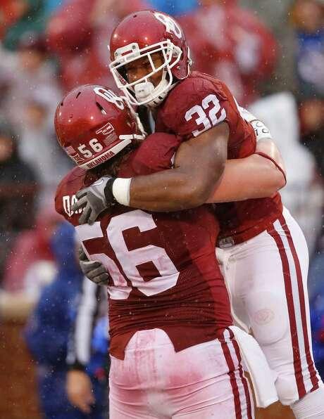 Samaje Perine (32) was a load for Kansas and teammate Ty Darlington. Photo: Sue Ogrocki, STF / AP