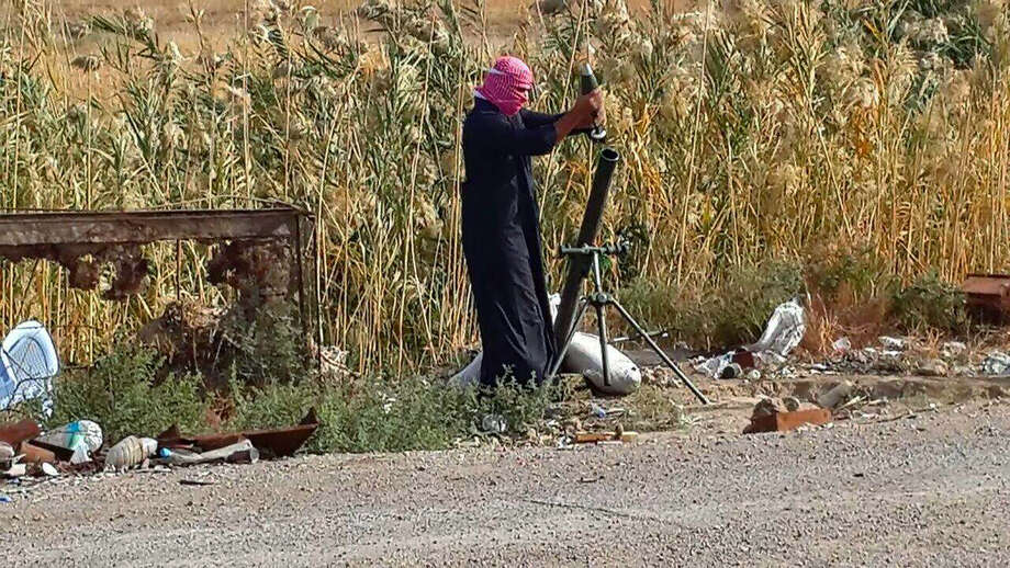 An Islamic State group fighter loads a mortar shell Saturday during clashes with Iraqi security forces in Ramadi. Iraqi soldiers backed by Sunni fighters launched a major operation to retake a section of Ramadi. Photo: Uncredited, STR / AP
