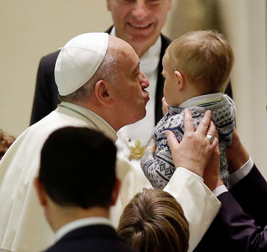 Pope Francis kisses a child as he meets with the participants at the missionary meeting of the Italian bishops' conference in the Paul VI hall at the Vatican, Saturday, Nov. 22, 2014. (AP Photo/Gregorio Borgia) Photo: Gregorio Borgia, STF / AP