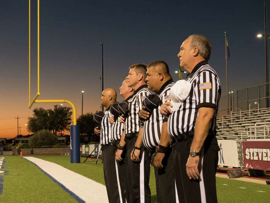 High school football officials Charlie Salinas Jr., left, Alan Kwast, Jeff Spence, Charlie Salinas Sr. and Charlie Wernette pay their respects during the playing of the national anthem before the Marshall-Brandeis game at Farris Stadium on Oct. 17, 2014. Photo: Billy Calzada /San Antonio Express-News / San Antonio Express-News