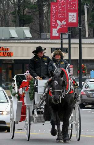 Alan Finney and Kimberly Revet of Saratoga Horse and Carriage and horse Annie give the first ride of the day to Joanne McGraw of Saratoga dressed as Mrs. Claus as complimentary seasonal horse-drawn carriage rides are offered during the Stuyvesant Plaza open house on Saturday Nov. 22, 2014 in Guilderland, N.Y. (Michael P. Farrell/Times Union) Photo: Michael P. Farrell / 00029594A