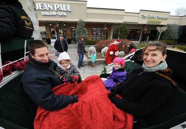 Joseph and Paige Pierle with daughters Ivy, 1-year-old, and Lena, 5-years-old, of Guilderland take a complimentary seasonal horse-drawn carriage ride during the Stuyvesant Plaza open house on Saturday Nov. 22, 2014 in Guilderland, N.Y. (Michael P. Farrell/Times Union) Photo: Michael P. Farrell / 00029594A