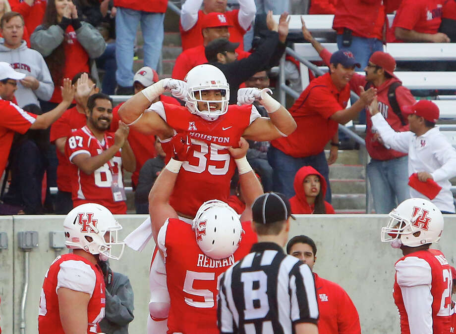 With an assist from lineman Bryce Redman, UH's Kenneth Farrow flexes after providing another show of strength with one of his four touchdown runs. Photo: Cody Duty, Staff / © 2014 Houston Chronicle