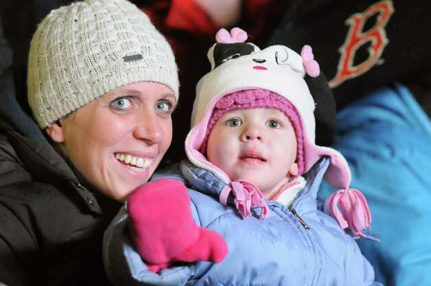Haley Osenko, 2, of Niskayuna, center, waves as she and her mother, Chrissy Penman-Osenko, watch the 47th Annual Gazette Holiday Parade on Saturday, Nov. 22, 2014, in Schenectady, N.Y. (Cindy Schultz / Times Union) Photo: Cindy Schultz / 00029203A
