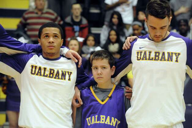 Elven-year-old JP Honsinger, center, who is suffering from rare childhood alzheimer's disease, lines up with the UAlbany basketball team during the national anthem  Wednesday night, Nov. 19, 2014, at SEFCU Arena in Albany, N.Y. (Michael P. Farrell/Times Union) Photo: Michael P. Farrell / 00029534A