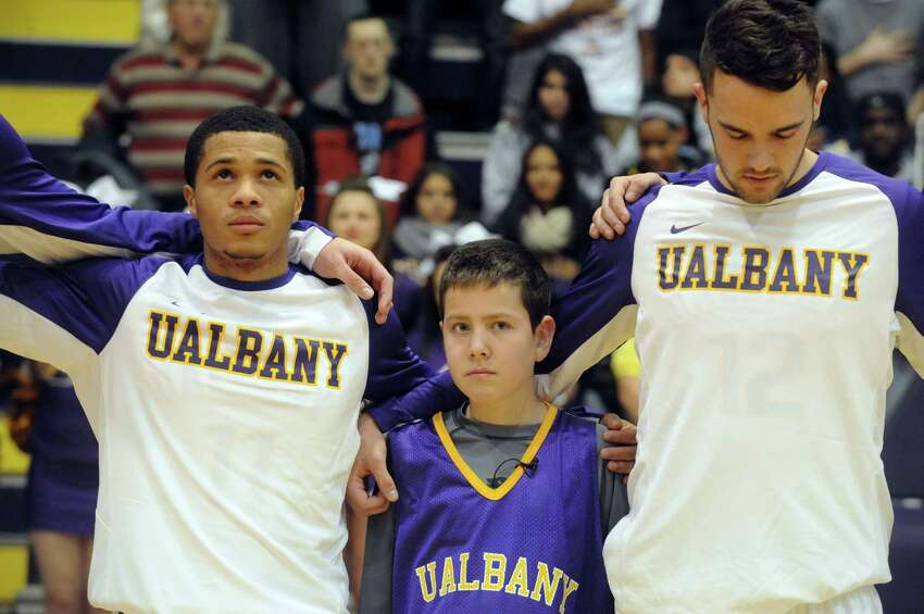 Elven-year-old JP Honsinger, center, who is suffering from rare childhood alzheimer's disease, lines up with the UAlbany basketball team during the national anthem Wednesday night, Nov. 19, 2014, at SEFCU Arena in Albany, N.Y. (Michael P. Farrell/Times Union)