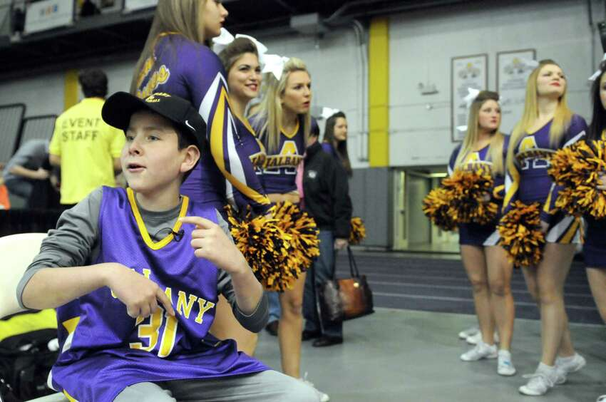 Elven-year-old JP Honsinger, left, who is suffering from rare childhood alzheimer's disease, sits on the UAlbany bench prior to UAlbany's men's basketball game against NJIT at the SEFCU Arena on Wednesday, Nov. 19, 2014, in Albany, N.Y. (Michael P. Farrell/Times Union)