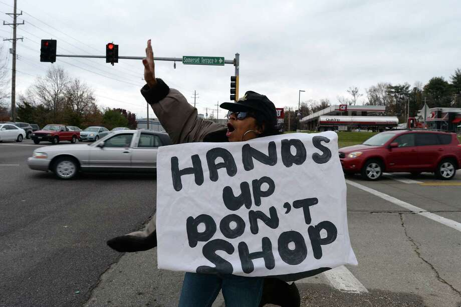 A woman urges people not to shop Saturday as she protests the death of 18-year-old Michael Brown in Ferguson, Mo. A grand jury still has not decided whether to indict a white police officer in the death of an unarmed black teenager. Photo: JEWEL SAMAD, Staff / AFP