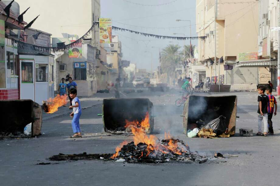 Clashes between police and anti-government protesters during Bahrain's first full election in nearly four years left burning debris in the streets. Photo: Hasan Jamali, STR / AP