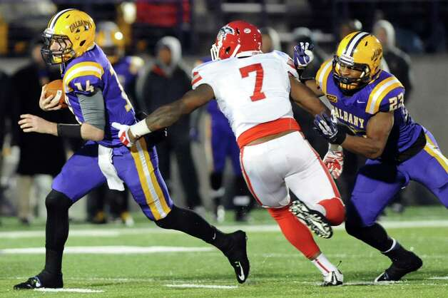 UAlbany's quarterback Will Fiacchi, left, gets some help from Omar Osbourne, right, as Stony Brook's Rahim Cassell defends during their football game on Saturday, Nov. 22, 2014, at Bob Ford Field in Albany, N.Y. (Cindy Schultz / Times Union) Photo: Cindy Schultz / 00029589A
