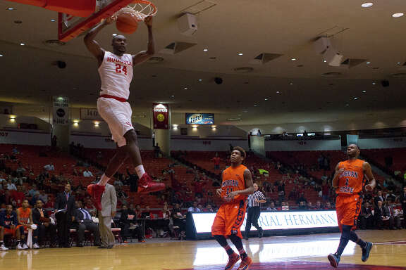 Houston Cougars forward Devonta Pollard dunks as Morgan State Bears guards Clive Vaughan Jr., center, and Donte Pretlow, right, look on during the first half of an AAC basketball game at Hofheinz Pavilion, Saturday, Nov. 22, 2014, in Houston.