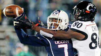 Connecticut cornerback John Green (7) breaks up the pass intended for Cincinnati wide receiver Alex Chisum (80) during the first half of an NCAA college football game in East Hartford, Conn., Saturday, Nov. 22, 2014.