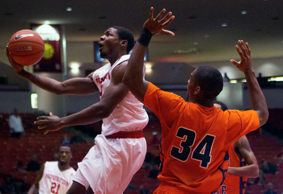 Houston Cougars guard Cavon Baker drives toward the basket as Morgan State Bears forward Cedric Blossom defends during the first half of an AAC basketball game at Hofheinz Pavilion, Saturday, Nov. 22, 2014, in Houston. (Cody Duty / Houston Chronicle) Photo: Cody Duty, Staff / © 2014 Houston Chronicle