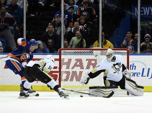 New York Islanders center Brock Nelson (29) shoots the puck past Pittsburgh Penguins center Brandon Sutter (16) and goalie Thomas Greiss (1) to score in the third period of an NHL hockey game at Nassau Coliseum on Saturday, Nov. 22, 2014, in Uniondale, N.Y. The Islanders won 4-1. (AP Photo/Kathy Kmonicek) ORG XMIT: NYI114 Photo: Kathy Kmonicek / FR170189 AP