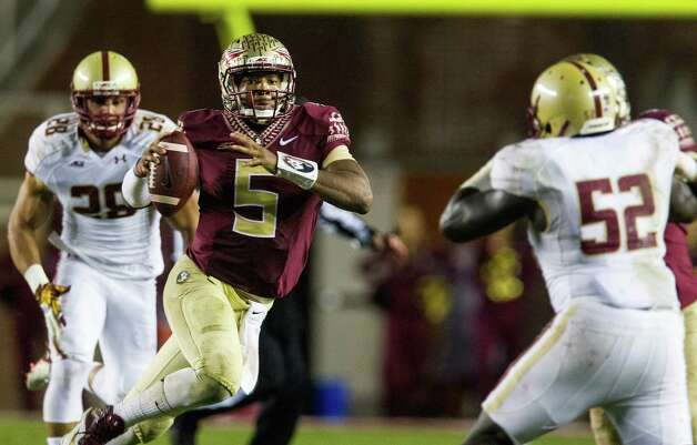 Florida State quarterback Jameis Winston, center, scrambles past Boston College defenders Matt Milano, left, and Steven Daniels in the second half of an NCAA college football game in Tallahassee, Fla., Saturday, Nov. 22, 2014. Florida State defeated Boston College 20-17.  (AP Photo/Mark Wallheiser) ORG XMIT: FLMW115 Photo: Mark Wallheiser / FR171224 AP