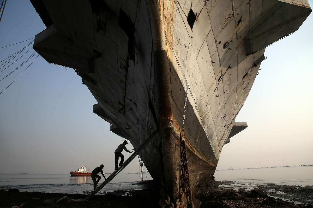 Workers climb to enter India's first aircraft carrier INS Vikrant to dismantle it at a ship-breaking yard in Mumbai, India, Saturday, Nov. 22, 2014. The iconic naval vessel, that was purchased from Britain in 1957, played a key role during the India-Pakistan war of 1971 and was decommissioned in 1997. (AP Photo/Rajanish Kakade)
